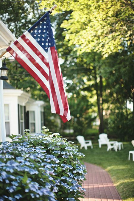 American flag attached to a white colonial home in Nantucket